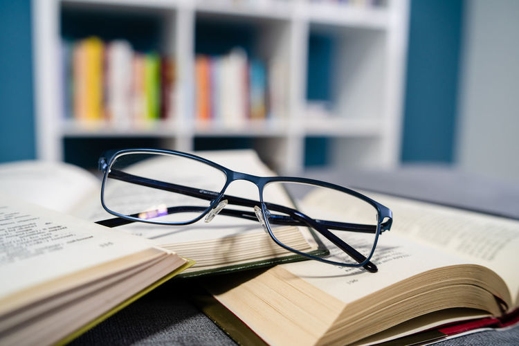 Book Publication Eyeglasses  Glasses Education Learning Table Indoors  Still Life Close-up Literature Open Selective Focus Expertise Paper No People Studying Wisdom Focus On Foreground Personal Accessory Bookshelf Reading Glasses Textbook Eyewear