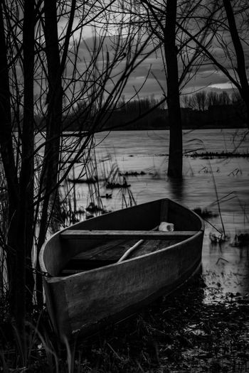 Boat moored by lake against sky