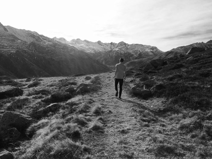 Full Length Rear View Of Man Walking By Mountains Against Sky