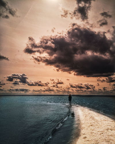 Woman standing on shore against sea during sunset