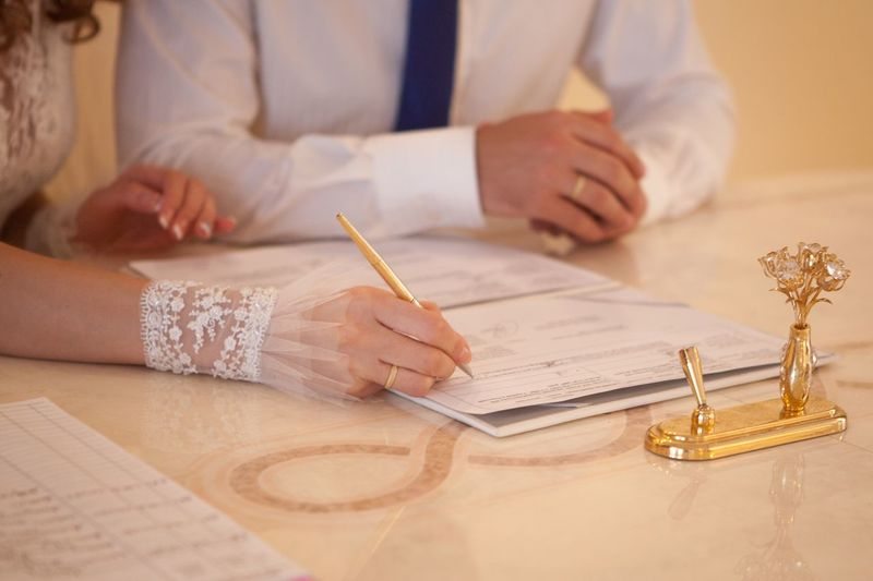 Midsection of bride signing document during wedding ceremony