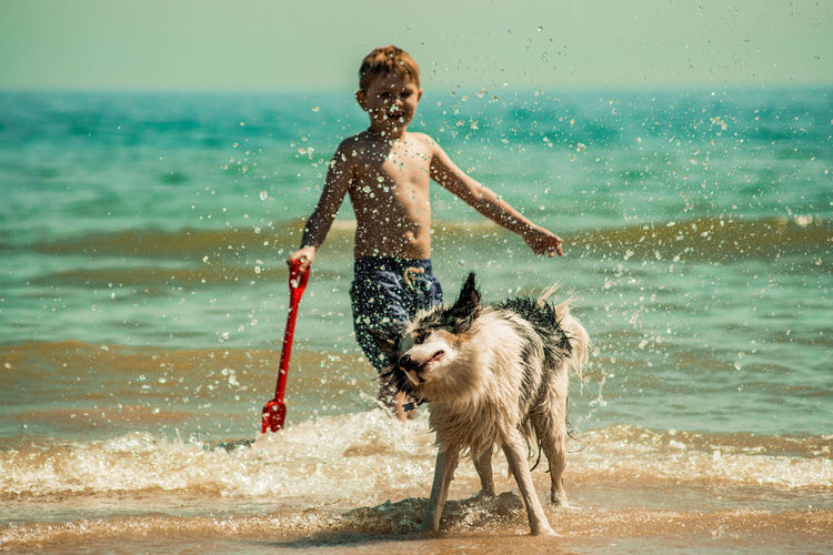 Shirtless boy with dog standing in sea against sky during sunny day