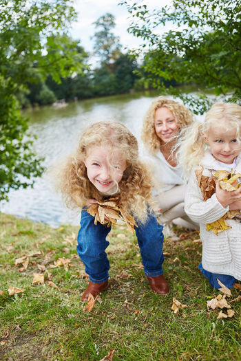 Sisters with mother collecting autumn leaves on field by lake