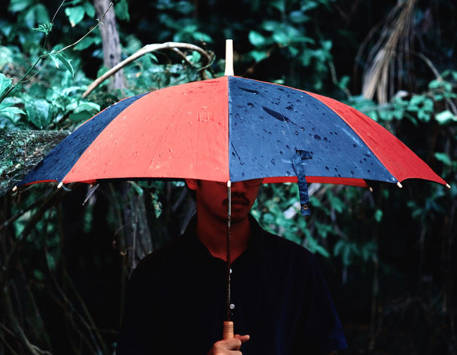 Man holding umbrella while standing by plants during rainy season