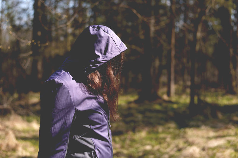 Side View Of Woman In Hooded Jacket Walking On Sunny Day