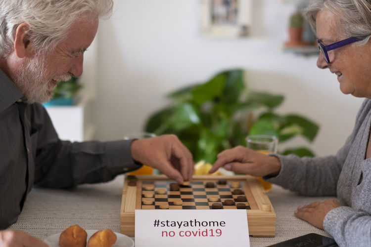 Side view of couple playing board game on table at home