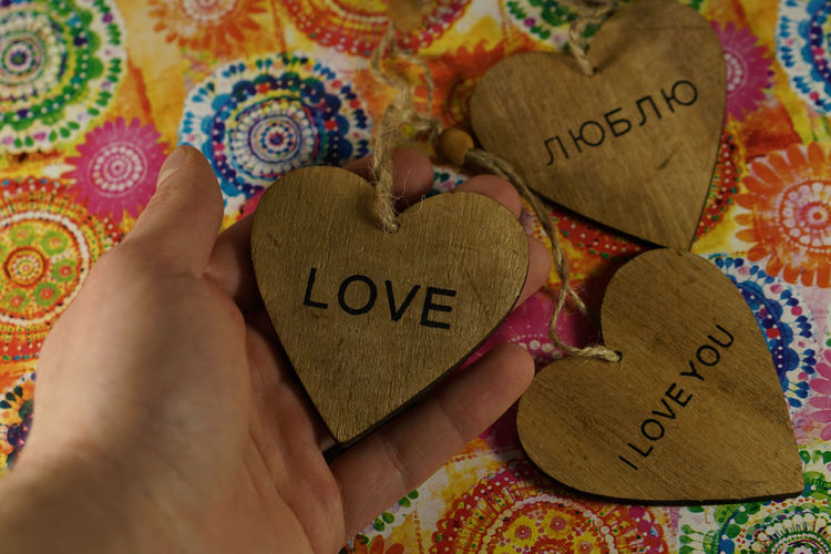 Cropped Hand Of Woman Holding Heart Shape With Love Text Over Table