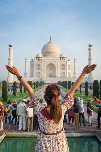 Girl with arms raised standing against taj mahal