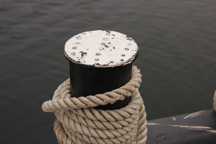 Close-Up Of Rope On Bollard Against Sea