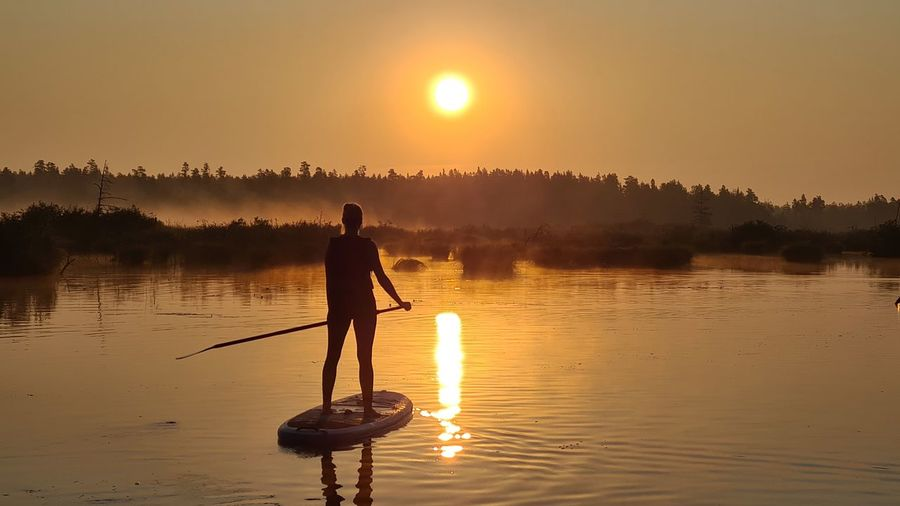 Rear view of woman standing in lake against sky during sunset. sunset on sup