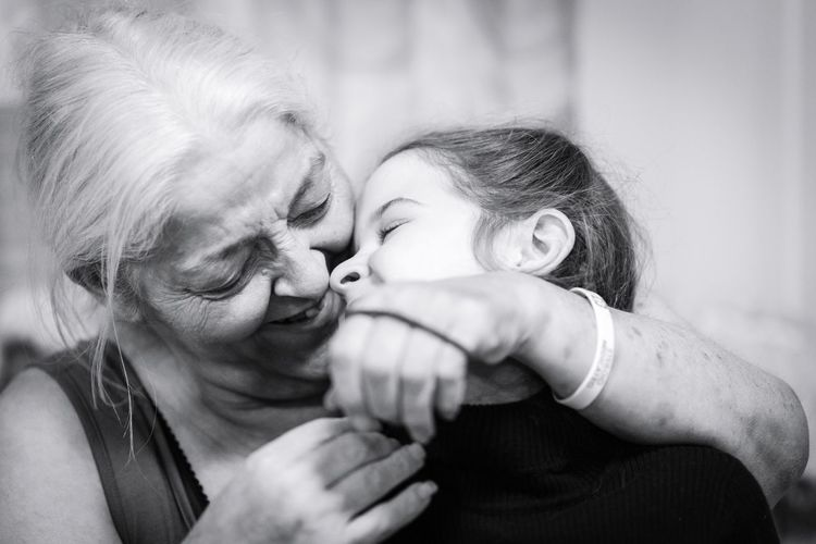 Close-Up Of Grandmother Embracing Granddaughter At Home