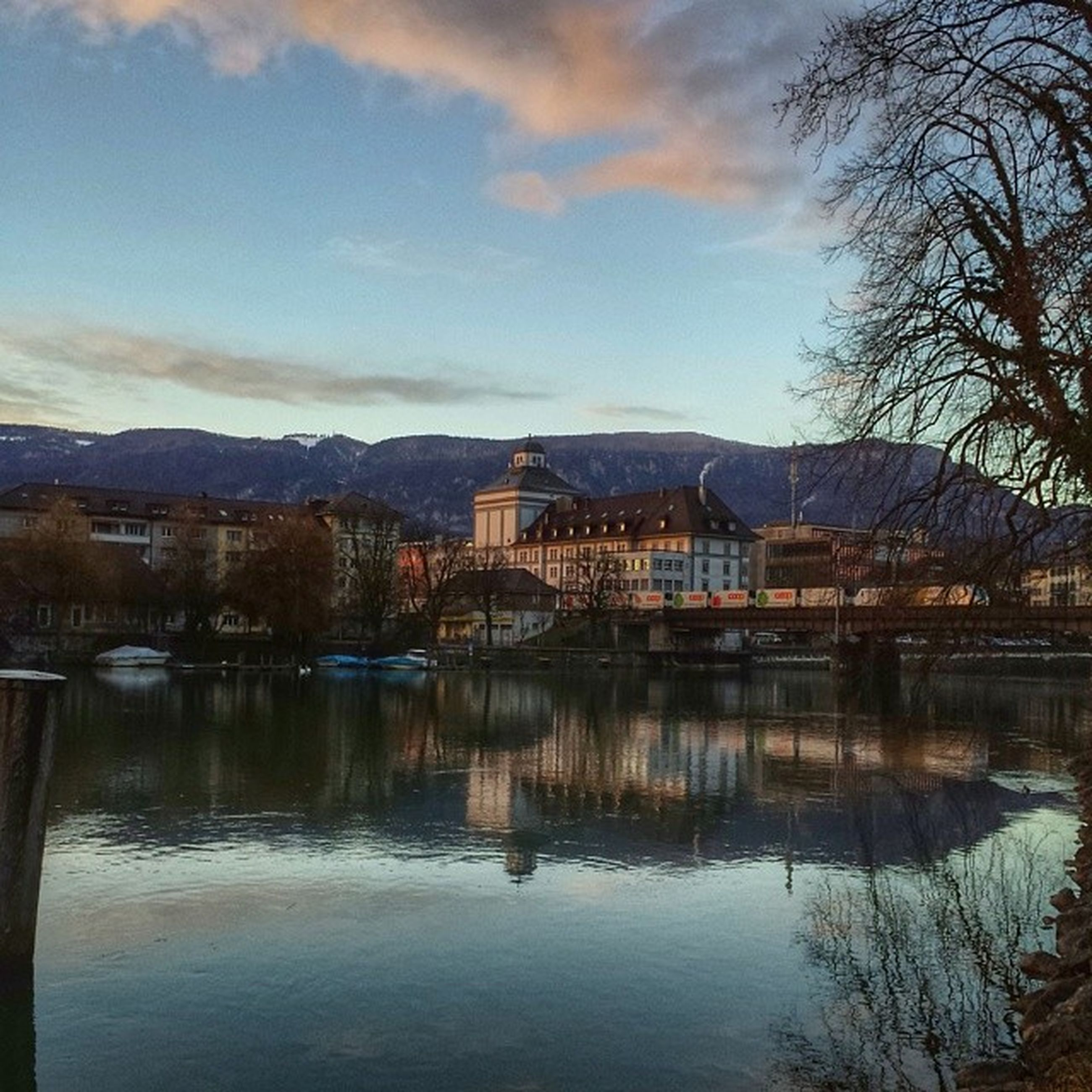 architecture, built structure, building exterior, water, reflection, mountain, sky, lake, house, waterfront, river, tree, mountain range, cloud - sky, tranquility, residential structure, town, tranquil scene, cloud, nature