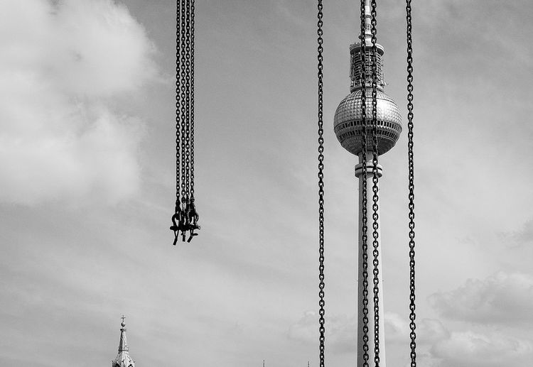 Low Angle View Of Fernsehturm Seen Through Chains Against Sky