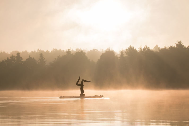 Silhouette person doing handstand in lake by trees against sky