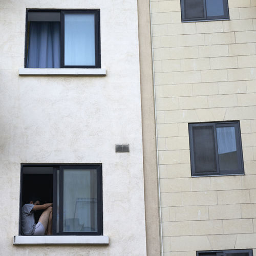 Low Angle View Of Man Sitting On Building Window Sill