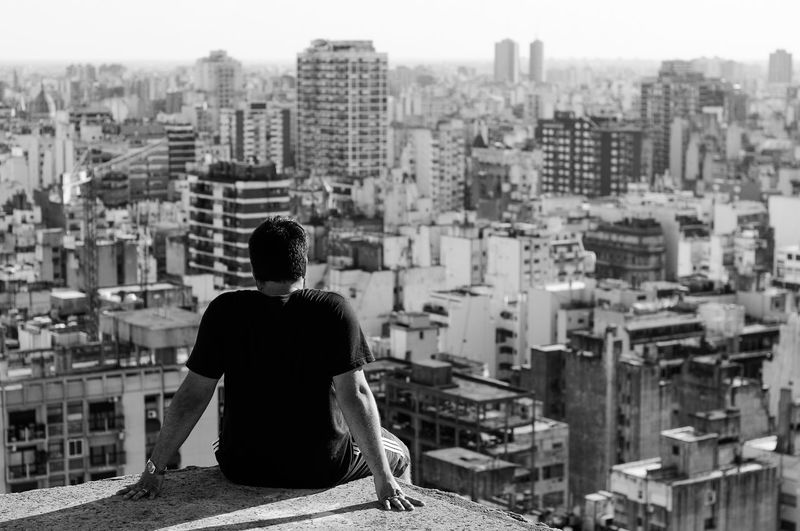 Rear view of man sitting on terrace overlooking cityscape