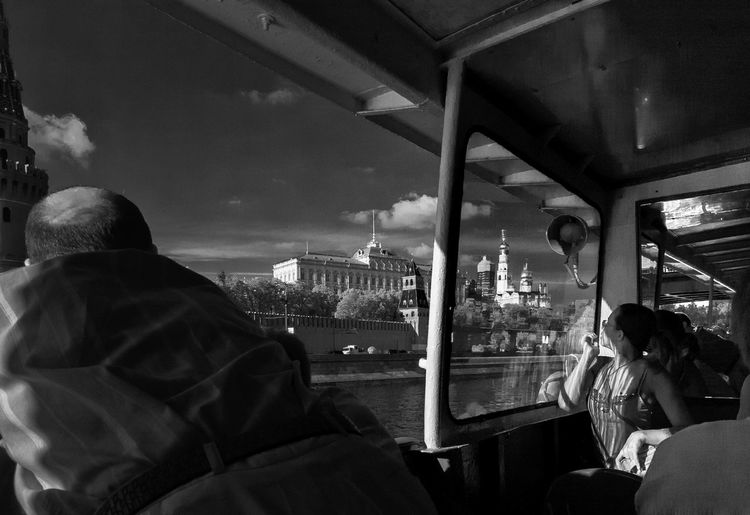 People in ferry boat over moskva river against sky