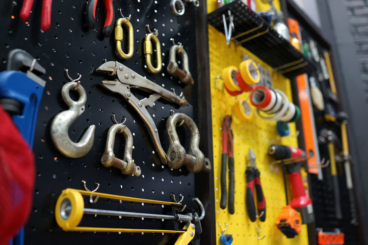 Work tools in a modern wall organizer Metal No People Close-up Equipment Industry Indoors  Work Tool Control Large Group Of Objects Yellow Choice Focus On Foreground Machinery Variation Tool Technology Workshop Connection Group Occupation Modern Organizer Wall Hanging Automobile Professional Concept Mechanic Garage Work Business Tape