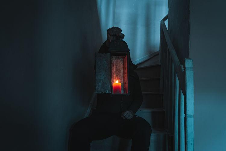 Man holding illuminated light on wall