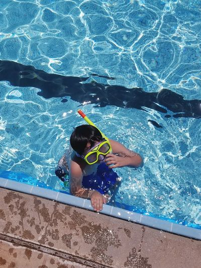 High angle view of boy with snorkel goggles and tube in swimming pool