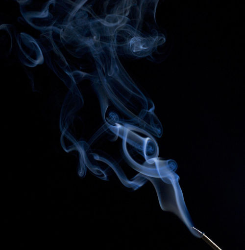 Incense stick smoke against black background