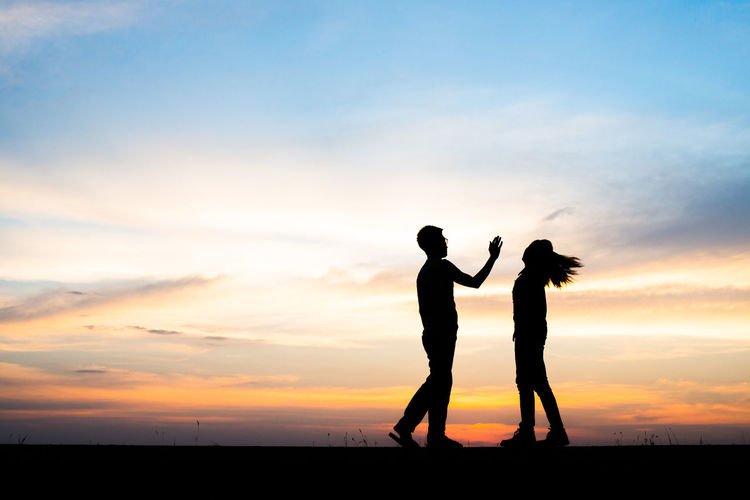 Silhouette Man Slapping Woman Against Sky During Sunset