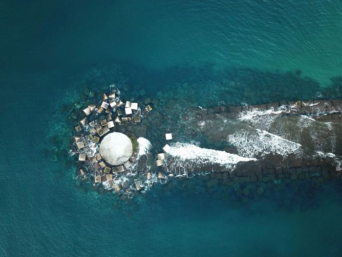 Aerial view of damaged pier in sea