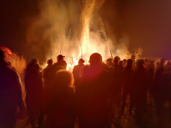 Rear view of people standing by bonfire at night