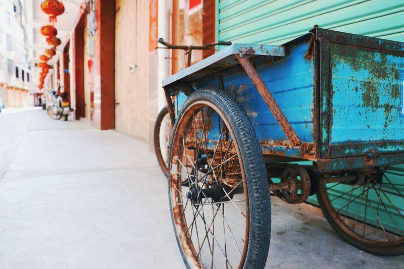 View of rusty rickshaw on street