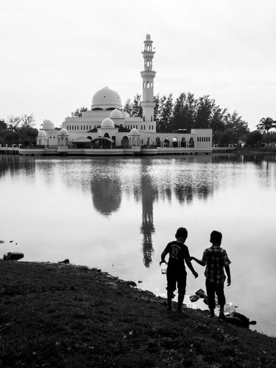 Two boys playing by the lake with a mosque and its reflection in the background Architecture Black And White Boys Day Floating Mosque Kuala Terengganu Lake Lakeside Masjid Masjid Tengku Tengah Zaharah Minaret Monochrome Photography Mosque Outdoors Playing Reflection Reflections Silhouette Two Two Boys Two People Water