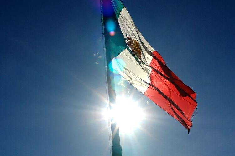 Low Angle View Of Mexican Flag Against Blue Sky