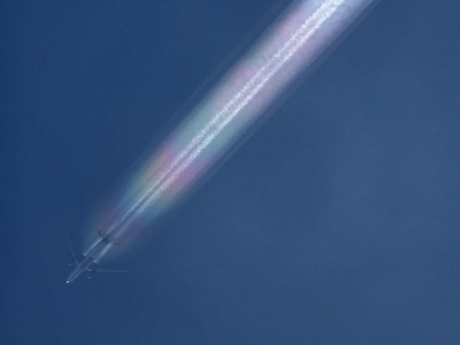 Contrail by negative pressure with rainbow colors Airplane Clear Sky Day No People Outdoors Sky Speed Transportation Vapor Trail