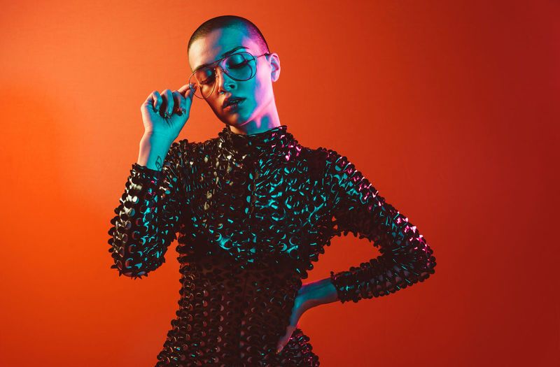 Young woman with shaved head wearing eyeglasses against orange background