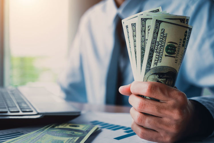 Midsection of businessman holding paper currency at desk in office