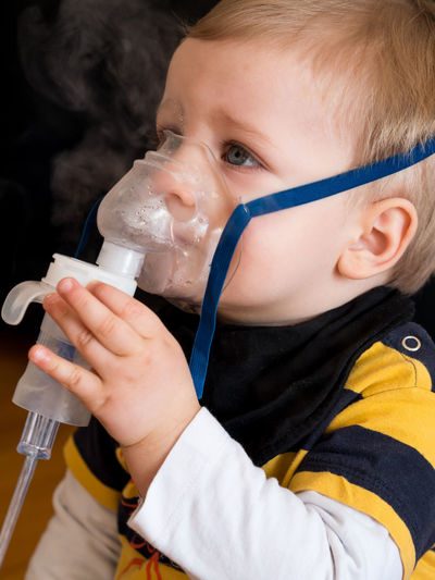 Small child in casual clothes taking inhalation in hospital Child Childhood Holding Indoors  Headshot Inhaling Boy Asthma Medical Oxygen Mask Health Medicine Treatment Allergy Patient Small Care Breath Respiratory Caucasian Kid Little Healthcare And Medicine Face Air Flu Close-up
