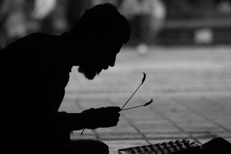 Close-up of man playing music on street