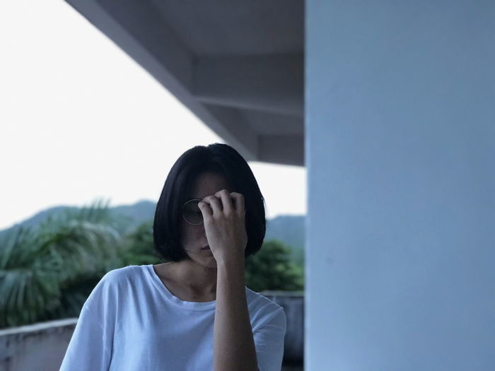 Young woman covering face at balcony