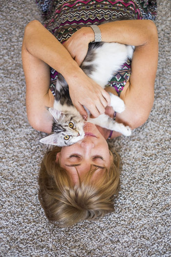 Unusual and mysterious portrait for a blonde caucasian woman with her cat in front of the face. Lying Down High Angle View Leisure Activity Relaxation One Person Lifestyles Women Domestic Blond Hair Real People Hair Domestic Animals Pets Furniture One Animal Directly Above Domestic Cat Pet Owner Hairstyle Purebred Cat Love Embracing Front View Aerial View Caucasian