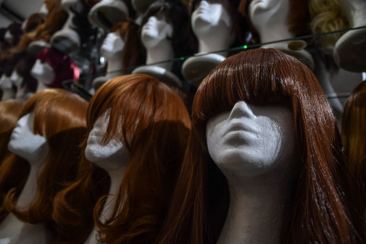 Close-up of wigs on mannequins in store