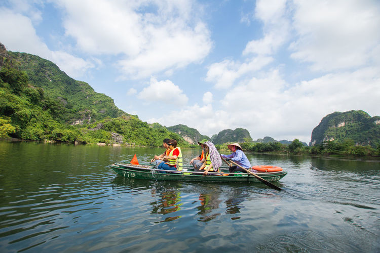 tourist sitting on boat at Trang An, Ninh Binh, Vietnam. Nautical Vessel Water Transportation Mode Of Transportation Waterfront Sky Real People Beauty In Nature Day Nature Group Of People Lifestyles Scenics - Nature Men River People Cloud - Sky Tranquil Scene Mountain Outdoors