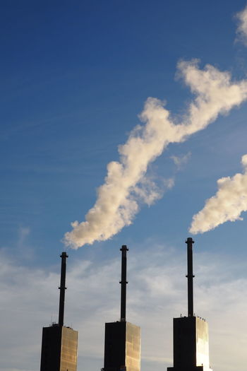 Low Angle View Of Smoke Stack Against Blue Sky