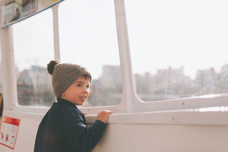 A little boy looking out the window of a boat. Mode Of Transportation One Person Window Transportation Looking Portrait Lifestyles Boy Child Boat