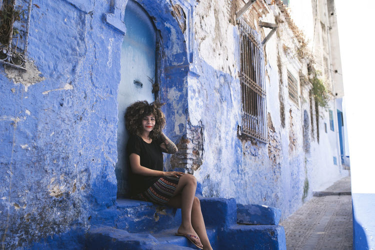 Architecture Beautiful Woman Blue Building Building Exterior Built Structure Casual Clothing Contemplation Day Full Length Hairstyle Leisure Activity Morroco One Person Outdoors Real People Side View Sitting Wall - Building Feature Window Women Young Adult Young Women