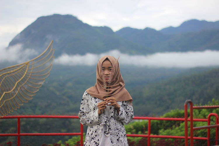 Portrait of woman wearing hijab holding crop against mountains