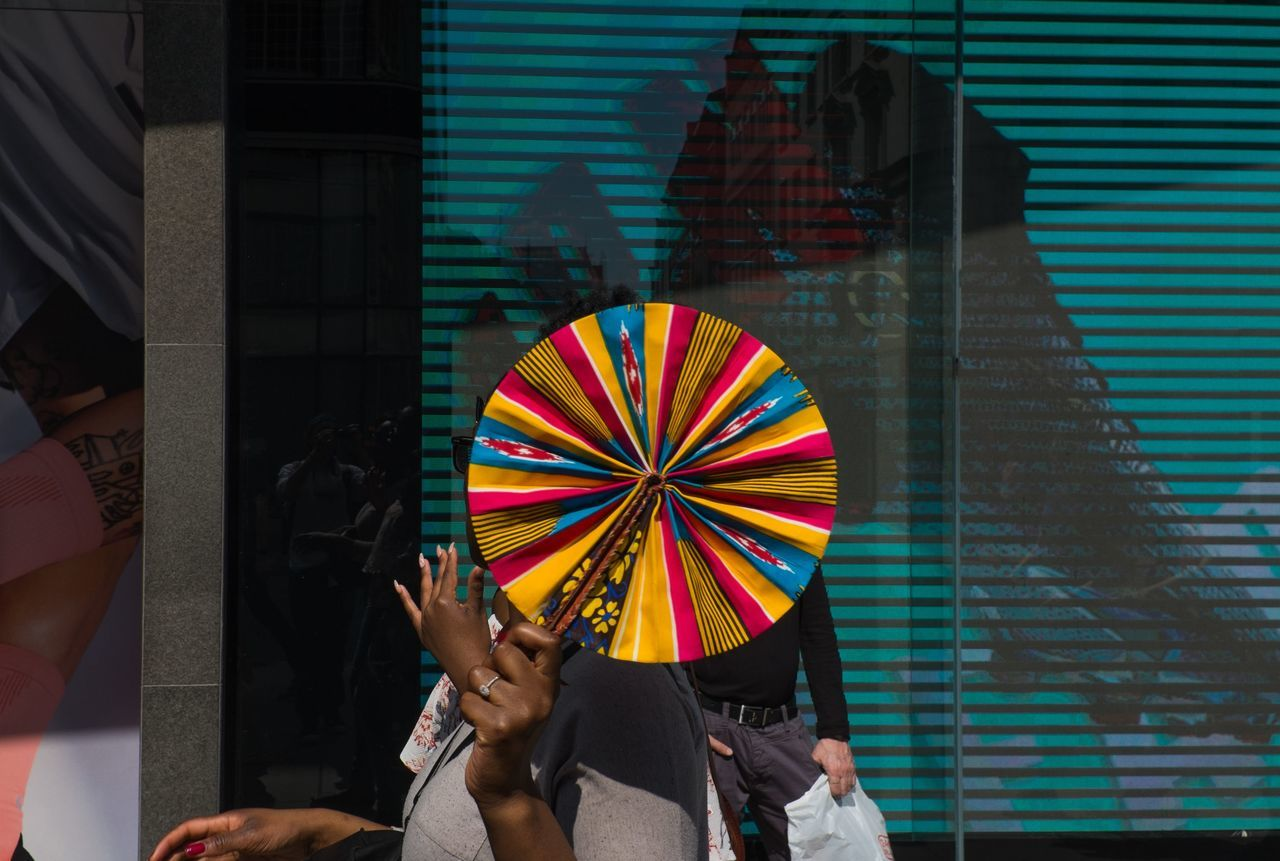 LOW SECTION OF PEOPLE HOLDING MULTI COLORED UMBRELLAS