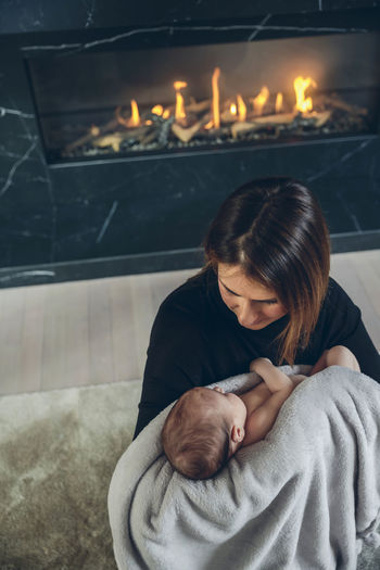 Mother with daughter sitting against fireplace at home