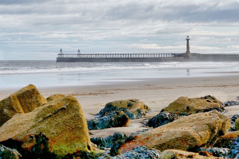 Whitby Lighthouse. Lighthouse Sea Beach Day Sand Outdoors Travel Destinations No People Rocks Ocean Yorkshire Lighthouse Whitby Seascape Travel Photography Landscape Clouds Sky Seaside