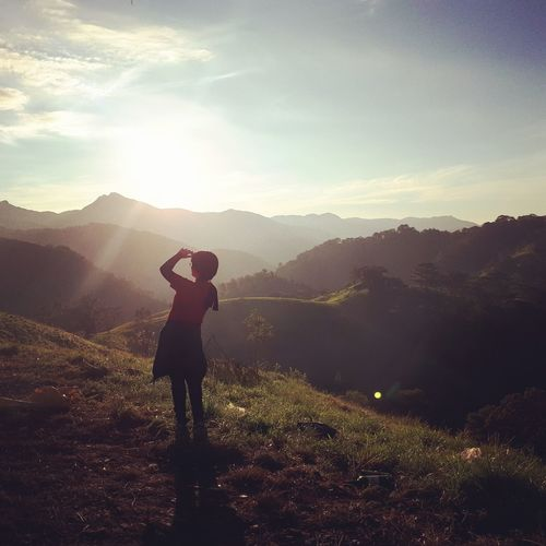 Rear view of woman shielding eyes while standing at mountain against sky during sunset