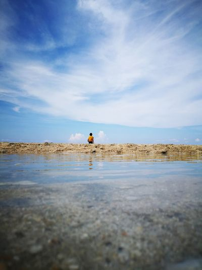 Surface level view of boy at beach against sky