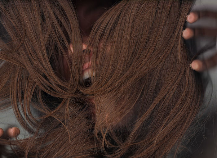 Close-up of woman face covered with brown hair